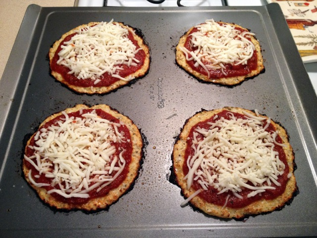 cooked cauliflower crust with tomato sauce and cheese