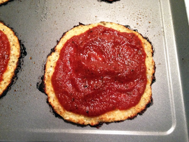 cooked cauliflower crust with tomato sauce close up